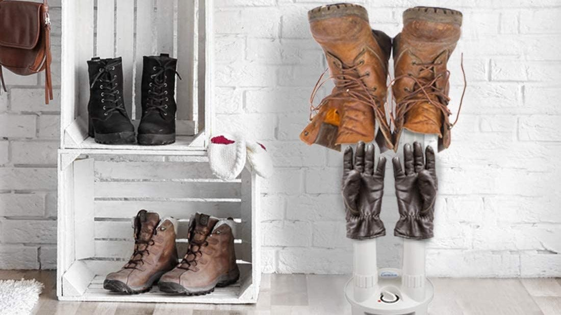 A pair of boots and gloves on the LAVIEAIR Boot Dryer, next to two apple crates, each with a pair of boots inside.