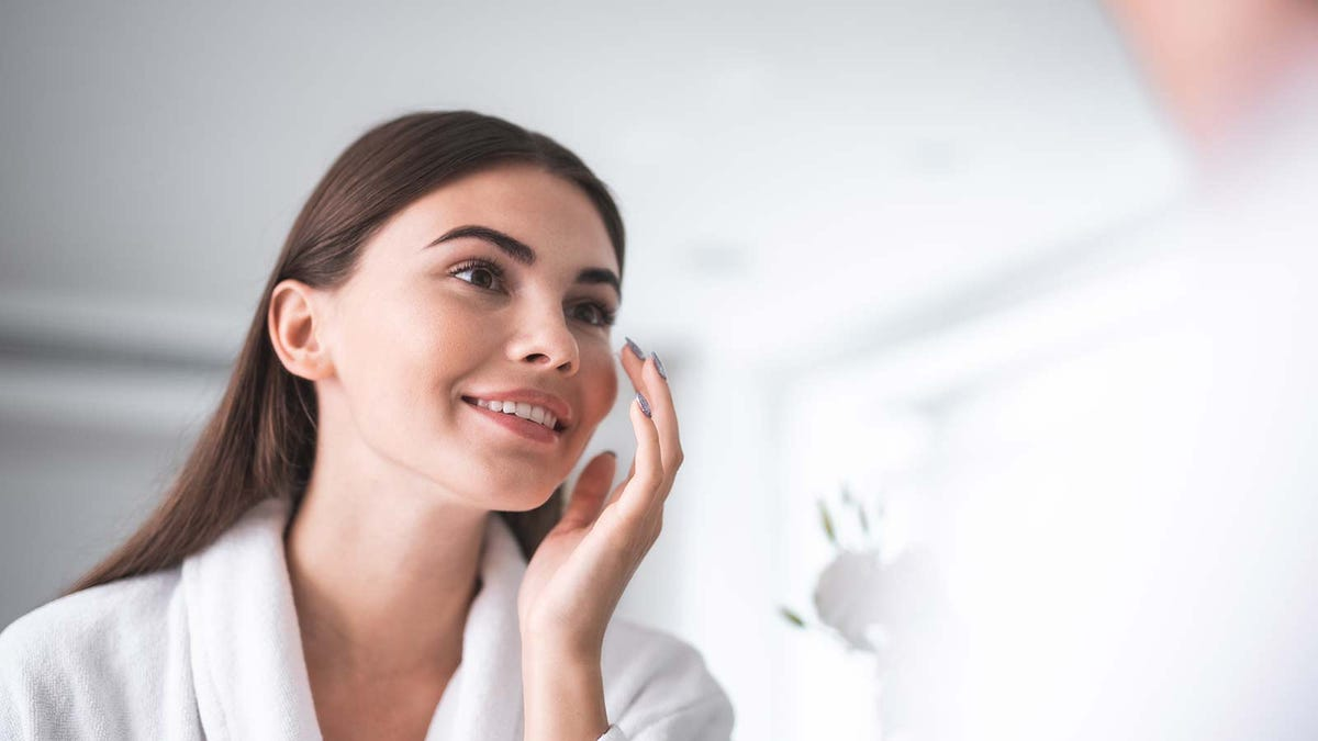 A woman putting facial serum on her face after using a beauty gadget on her skin.