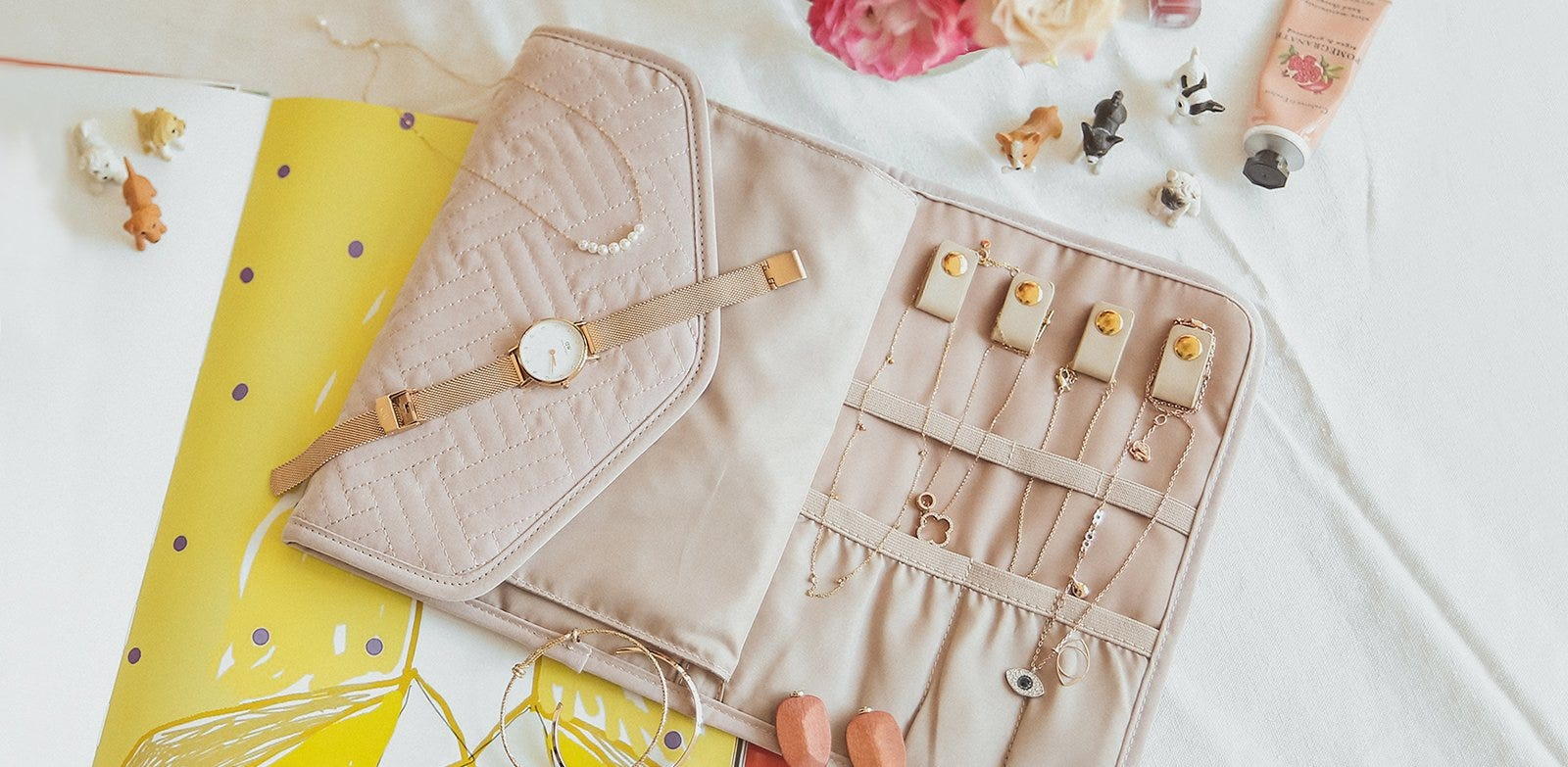 Folding jewelry case open to show jewelry inside.