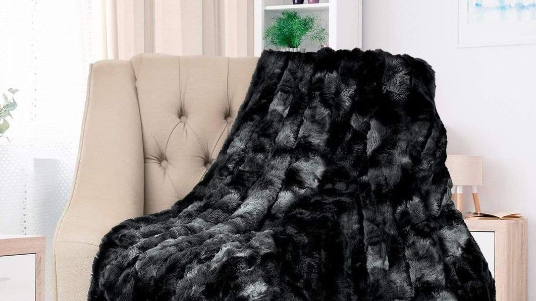 An Everlasting Comfort Faux Fur Throw in black draped over a cream chair.