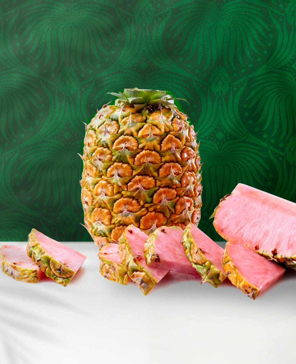 A pineapple sitting upright, surrounded by sliced pieces of pink pineapple.