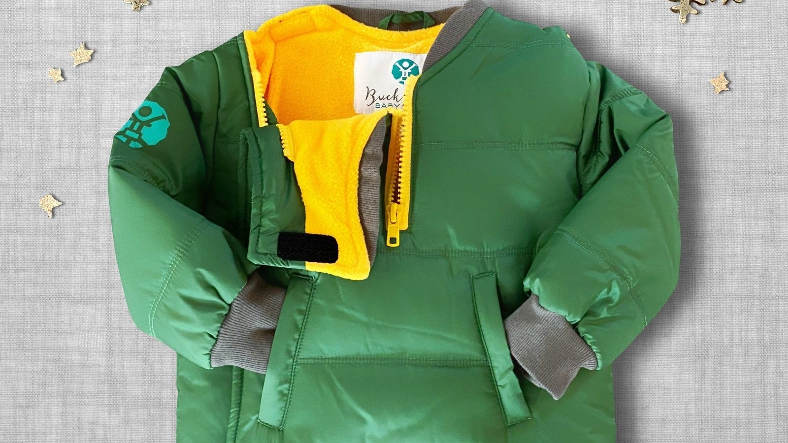 A green Buckle Me Baby Coat.