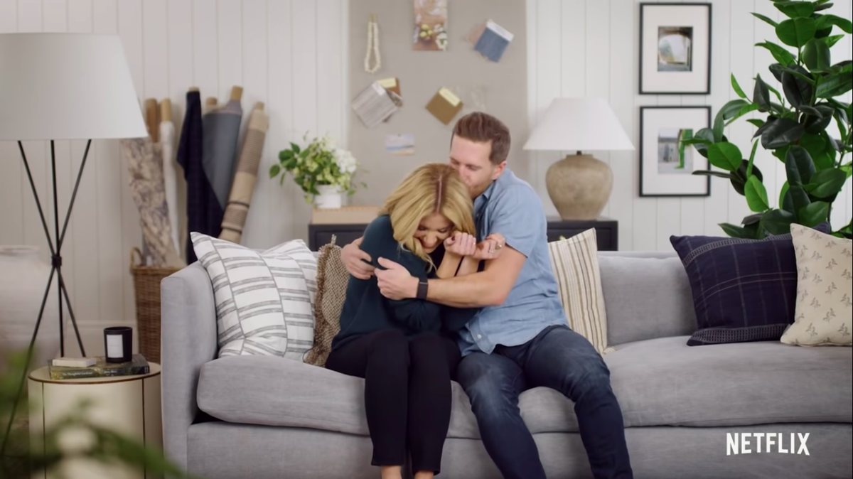 A man embraces a laughing woman as they sit on a couch.