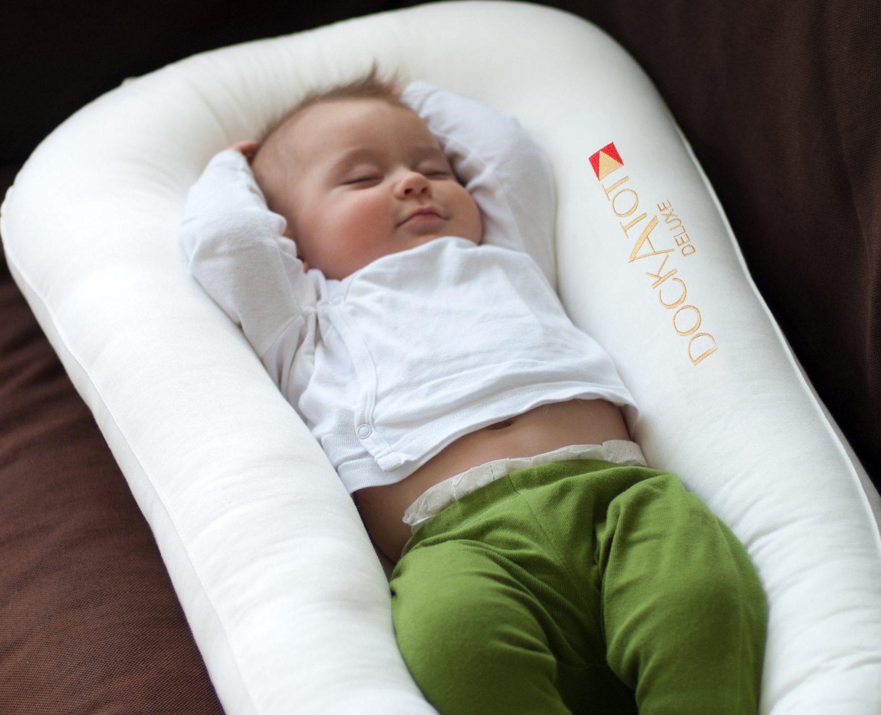 A baby sleeping on a white DockATot Nest.