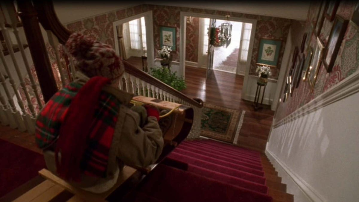 Kevin McCallister (Macauley Culkin) on a sled at the top of the stairs in 'Home Alone.'