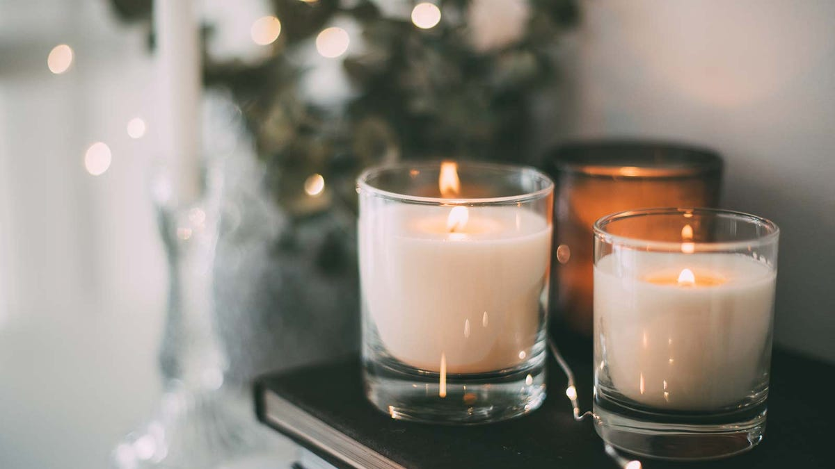 Three lit votive candles in glass holders sitting on a stack of books.
