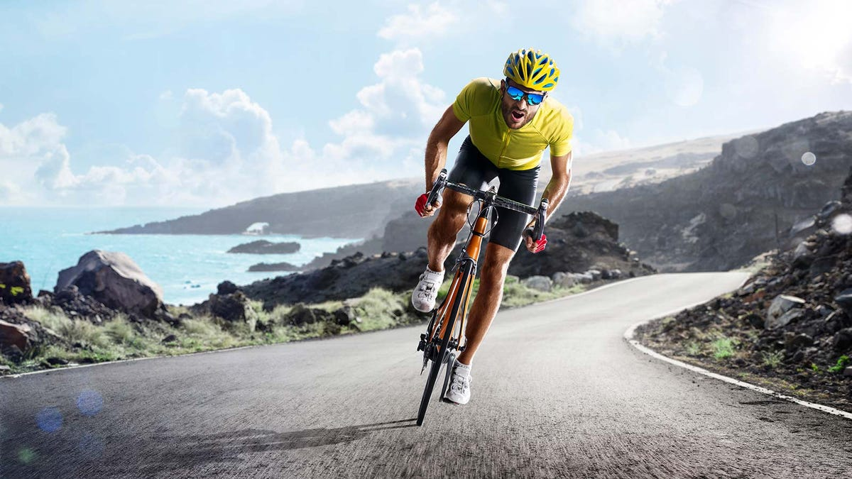 A male cyclist riding on a road next to the ocean.