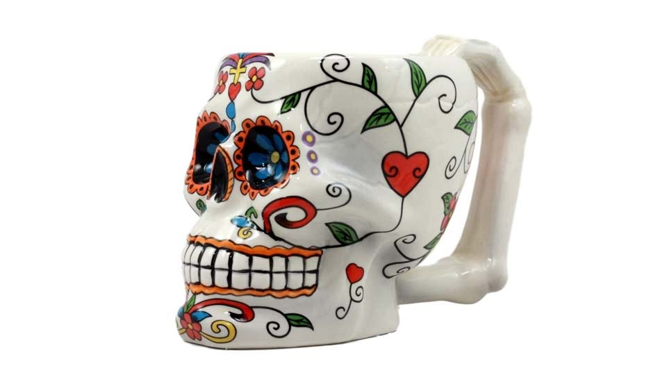 A skull mug decorated to look like a Mexican sugar skull.