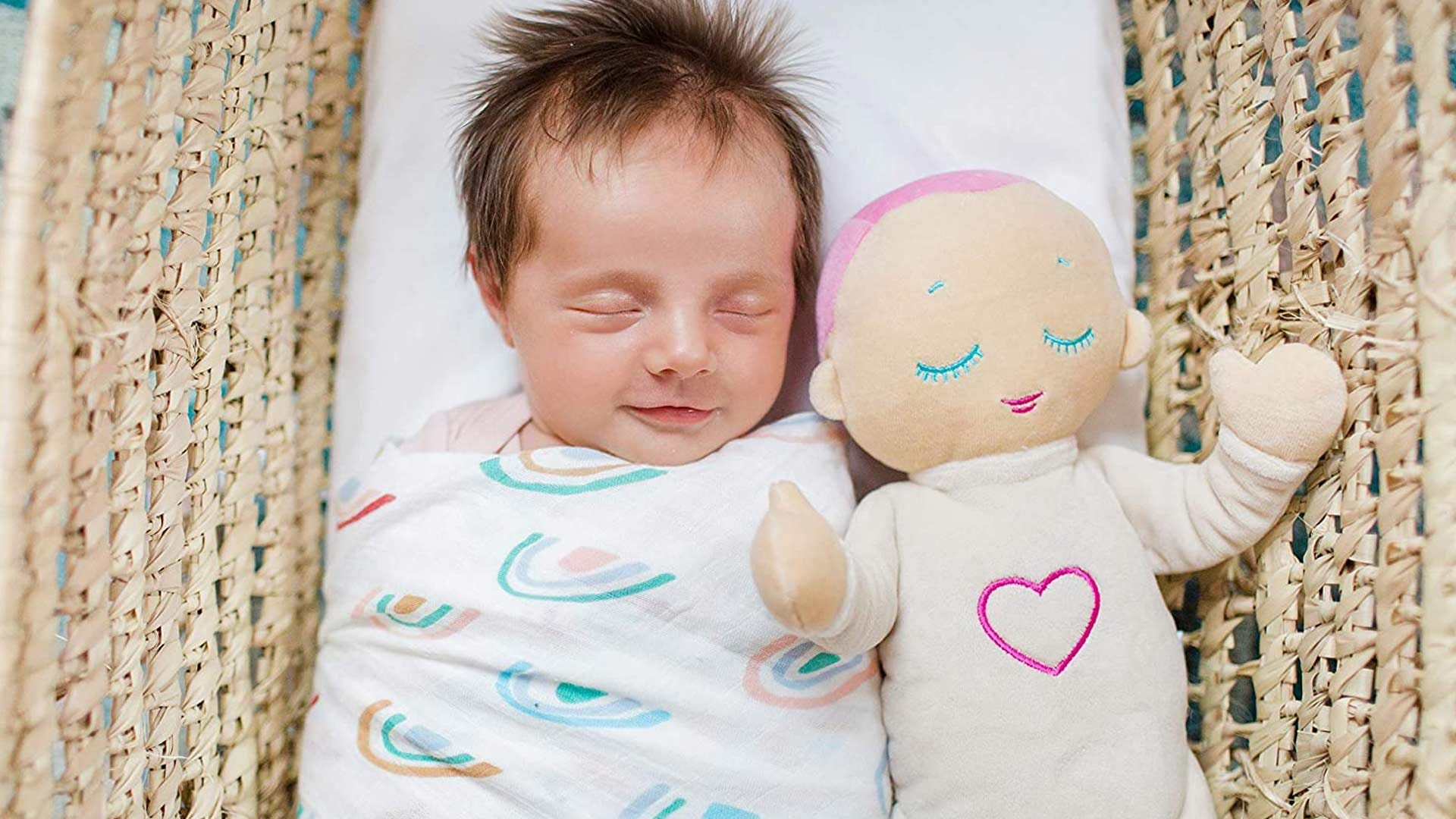 A baby sleeping with a soothing doll.