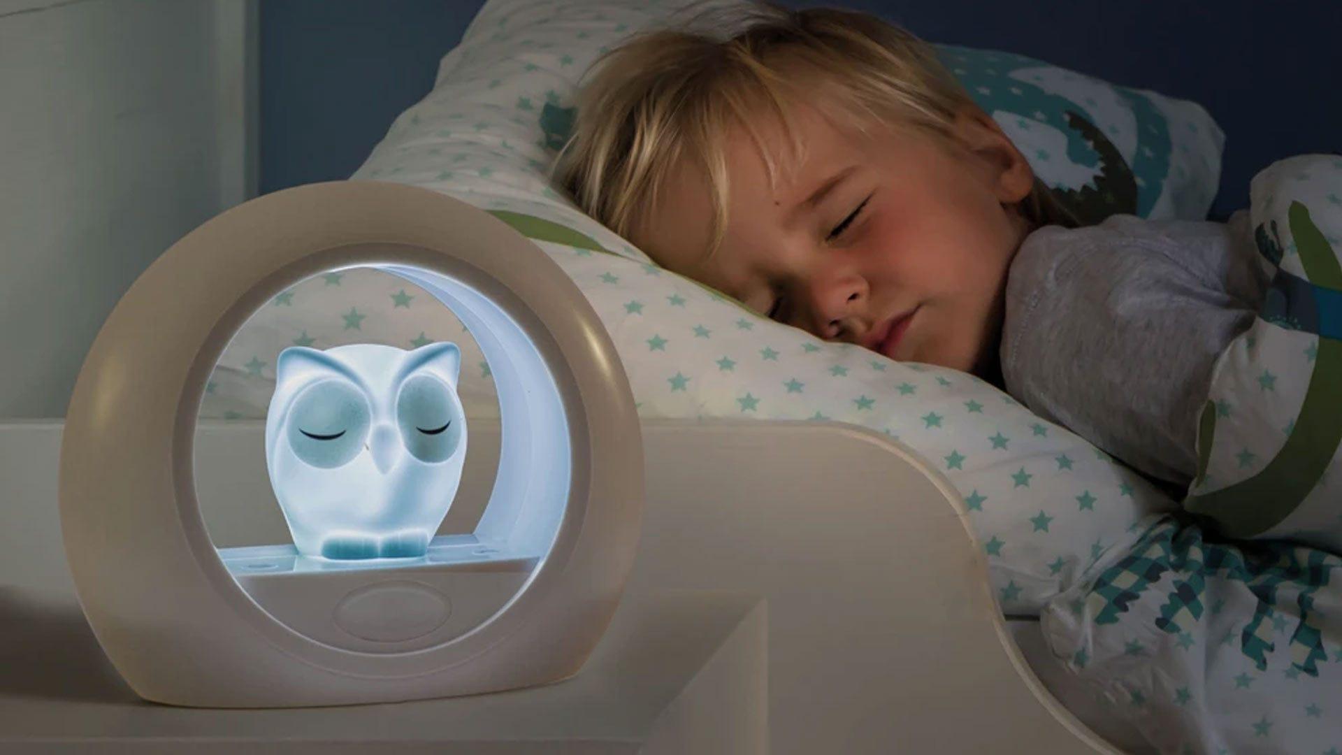 A boy sleeping with an owl nightlight.