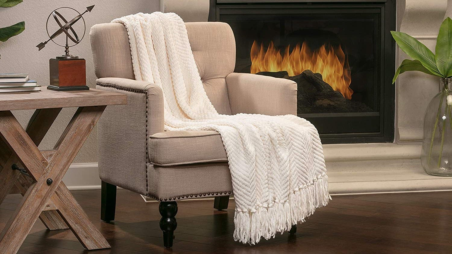 A white Chanasya blanket draped over the back of a chair in front of a fireplace.
