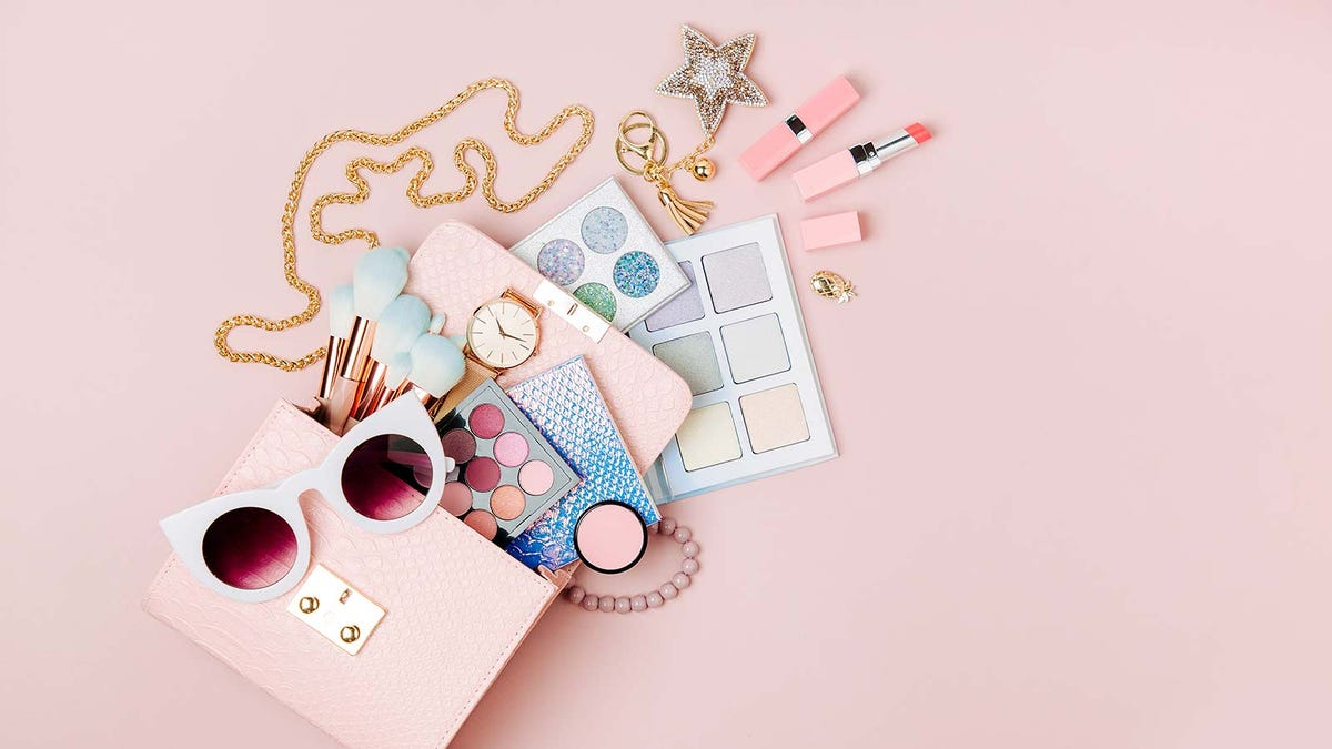 A pink purse with cosmetics and accessories pouring out.
