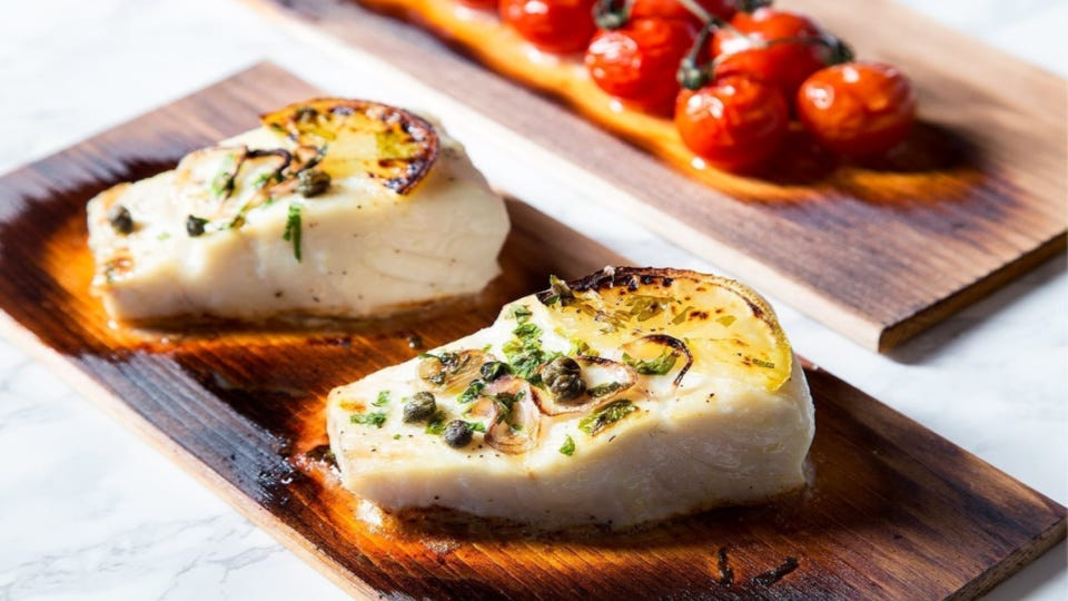 Two haddock filets seasoned with fresh herbs, capers, and lemon wheels, on a Wildwood Grilling plank.