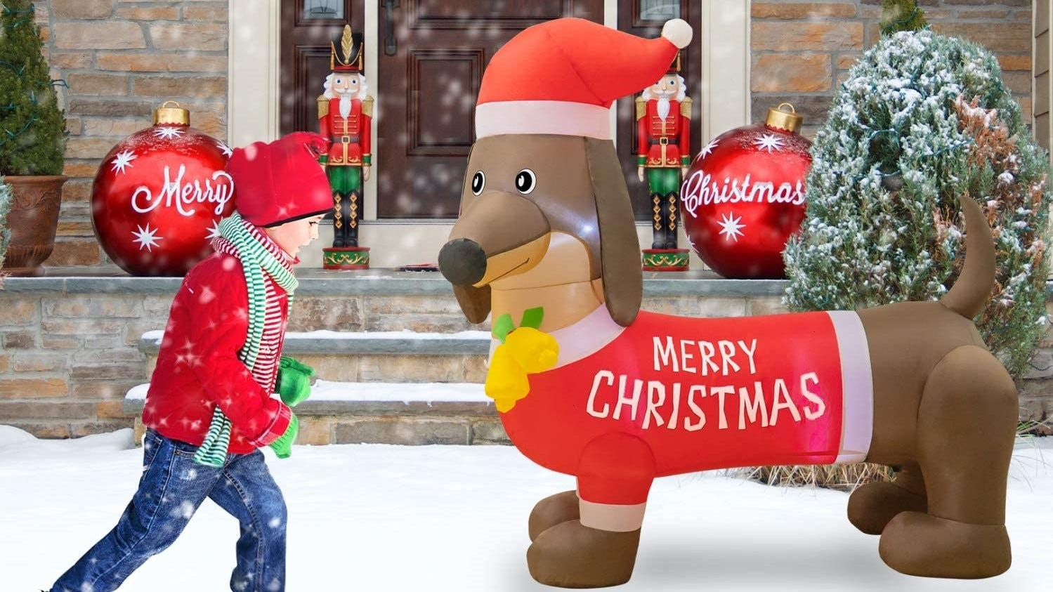 A child walking by an inflatable Christmas dog.
