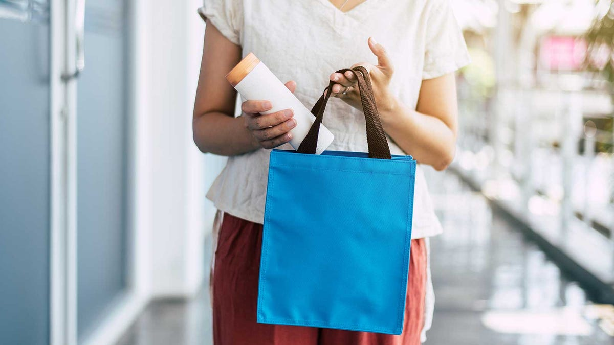 A woman putting a metal water bottle into a reusable tote.