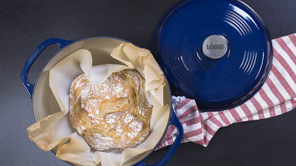 A brightly colored blue dutch oven, made by the Lodge company, with a fresh hot loaf of bread fresh out of the oven, displayed with a red and white linen.