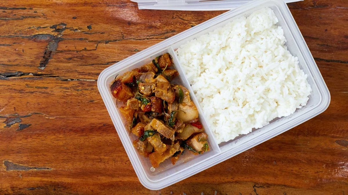 A two-part storage container is filled with meat and rice.