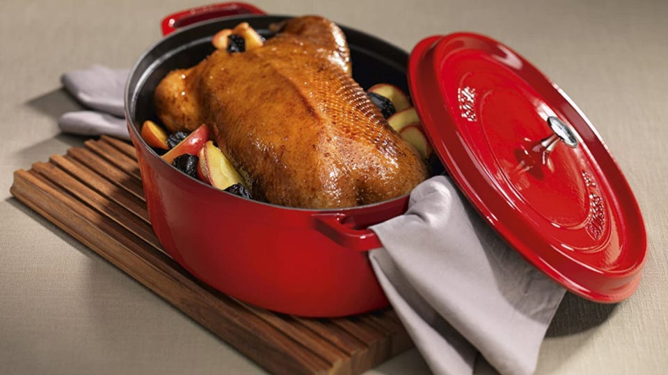 A red cocotte Dutch Oven filled with a lovely roasted turkey, surrounded by apples and prunes, displayed on a wooden board with two gray linens.