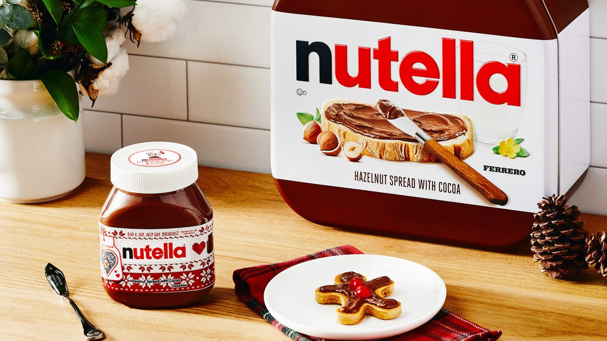 A jar of nutella and a pancake sit on a wooden countertop.