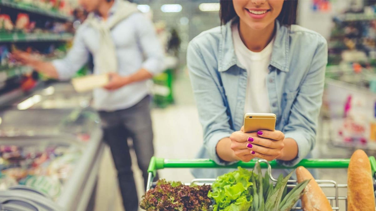 A woman looks at her phone as she pushes a grocery cart around a store.