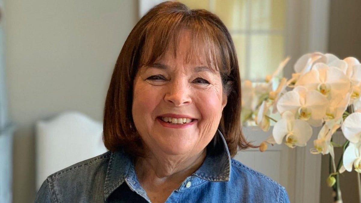 Ina Garten stands by a table holding her latest cookbook.