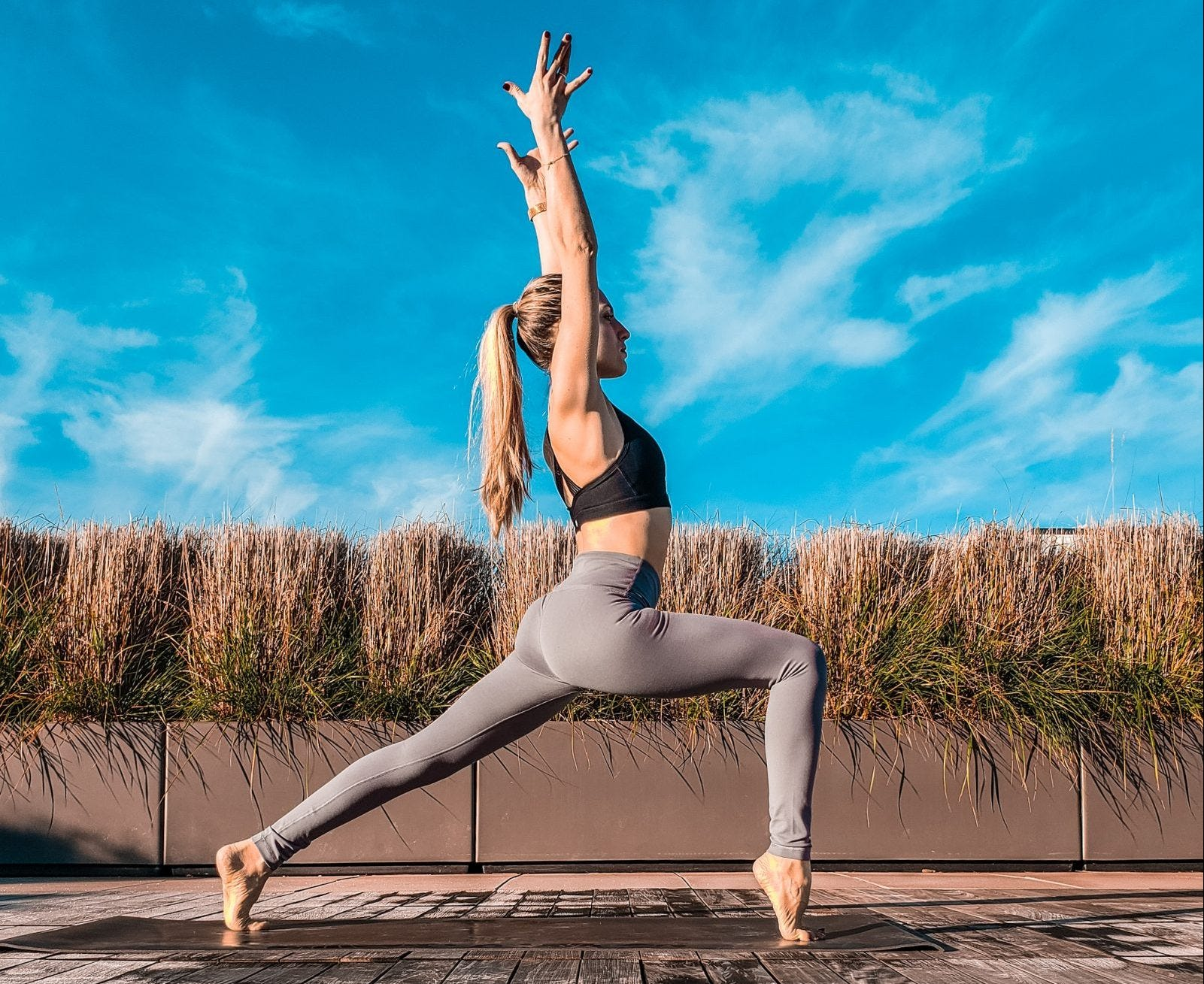 A woman doing a high lunge pose outdoors.