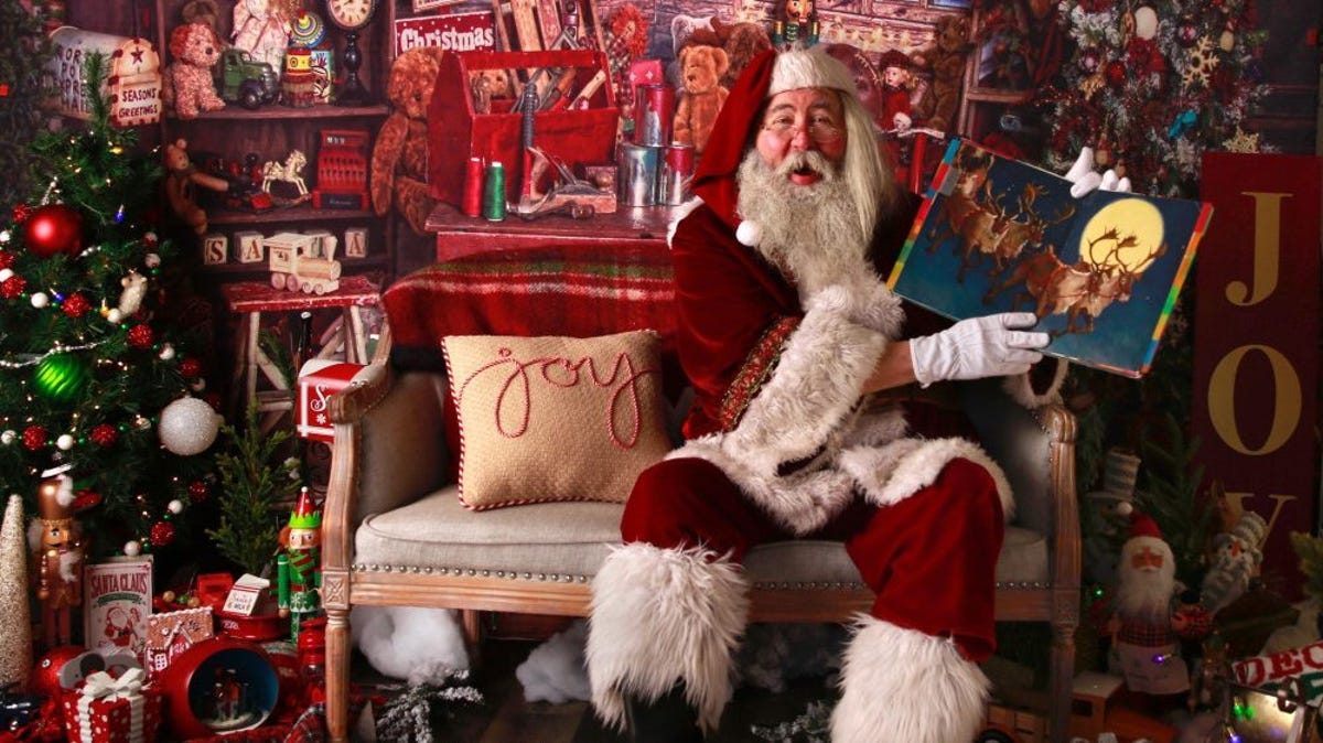 A Santa Claus sits in a cozy cabin and reads a book.