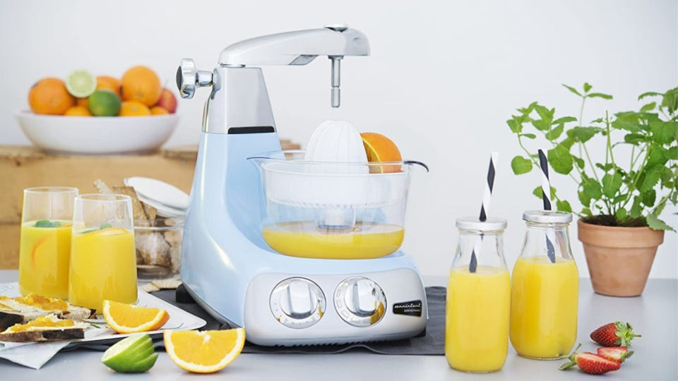 A pristine Ankarsrum mixer filled with freshly squeezed orange juice, surrounded by oranges, limes and cold glasses of juice.
