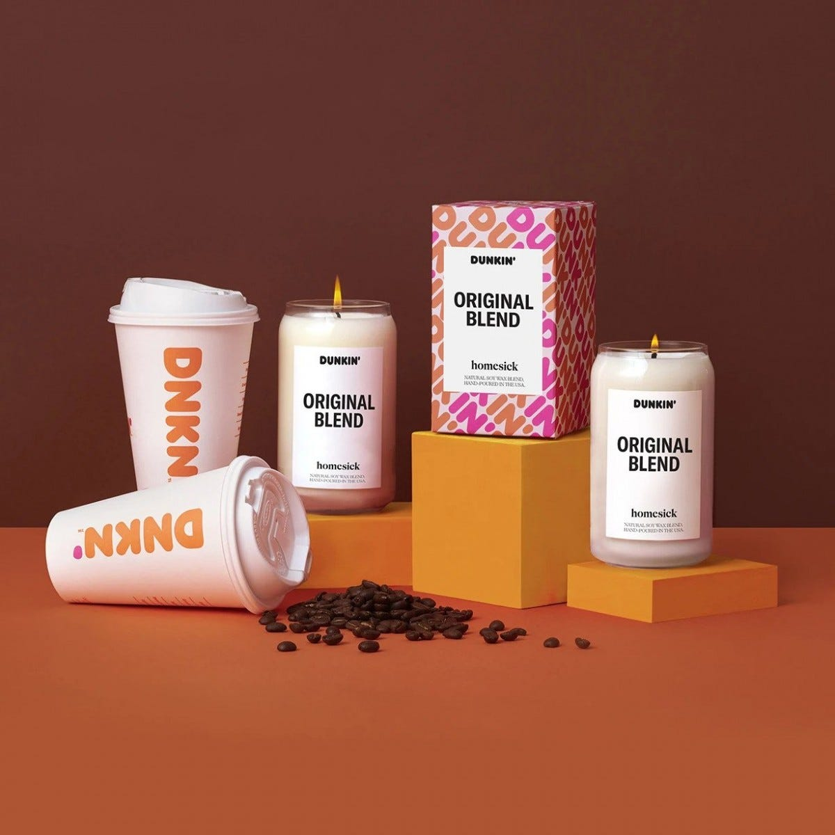 A collection of Dunkin' candles sit arranged among cups and coffee beans.