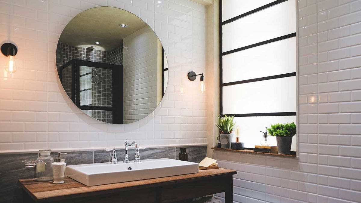 A bathroom with a large and beautiful mirror hanging over the sink.