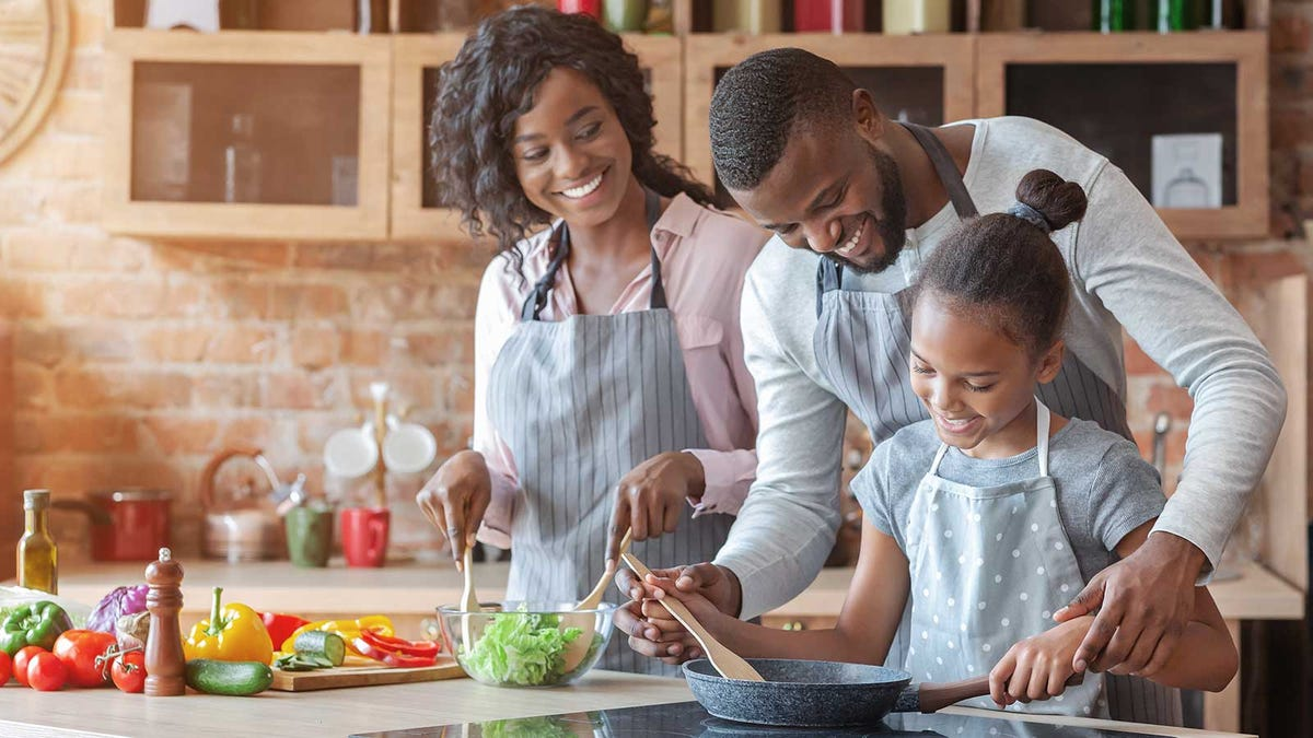 A family cooking in a sunny kitchen.