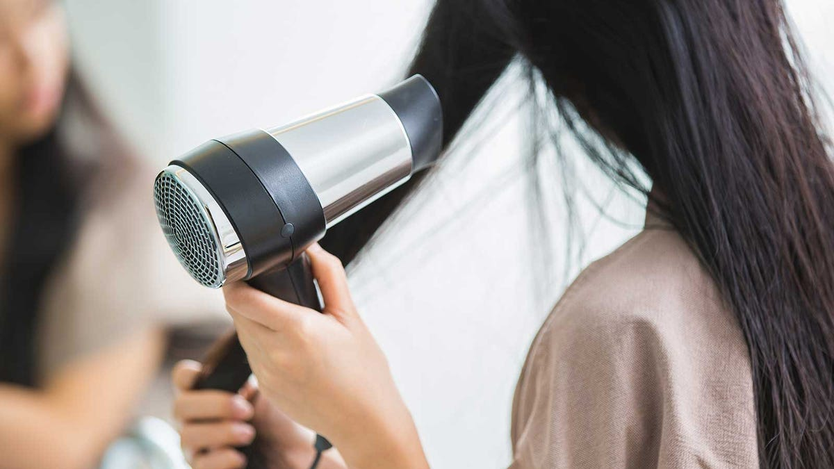 A woman blow drying her hair.