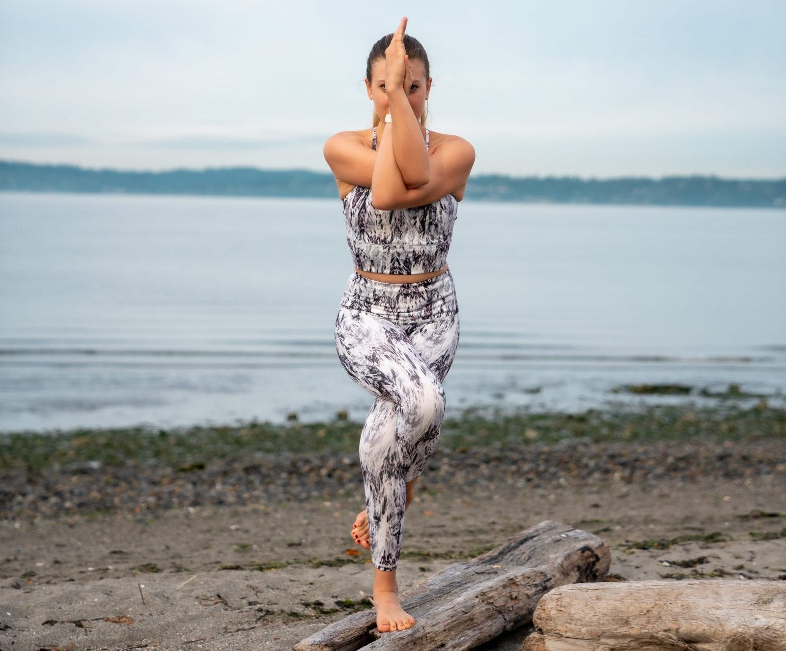 A woman doing an eagle yoga pose on the beach.