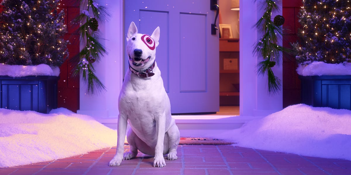 A white terrior with a bulleyes eye around his eye sits in front of a door.