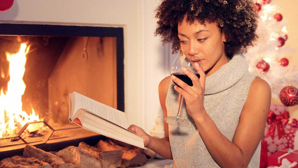 A woman drinking wine and reading a book by a fireplace at Christmas.