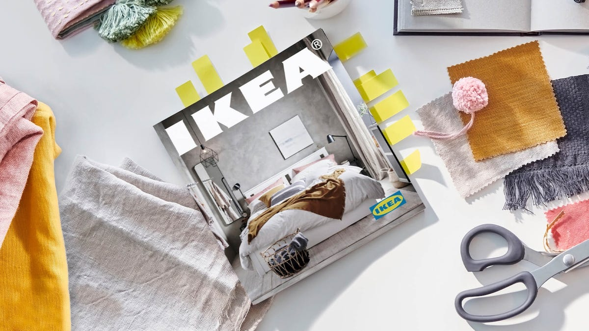 An IKEA catalogue sits among fabric and scissors on top of a desk.
