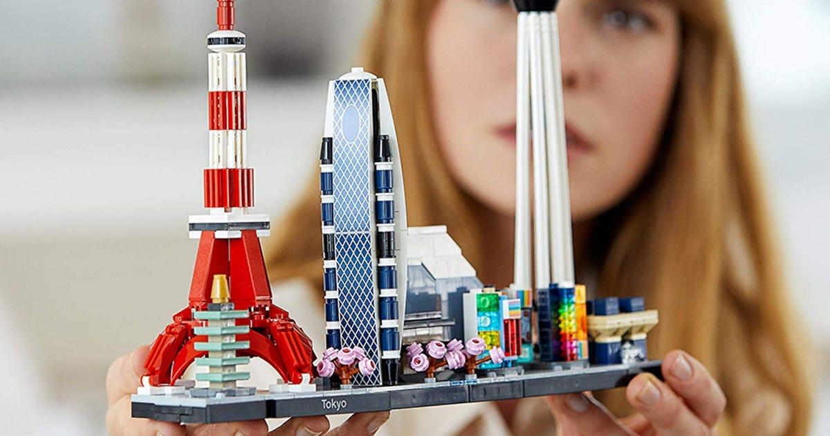A woman holding the Tokyo Skyline LEGO creation.