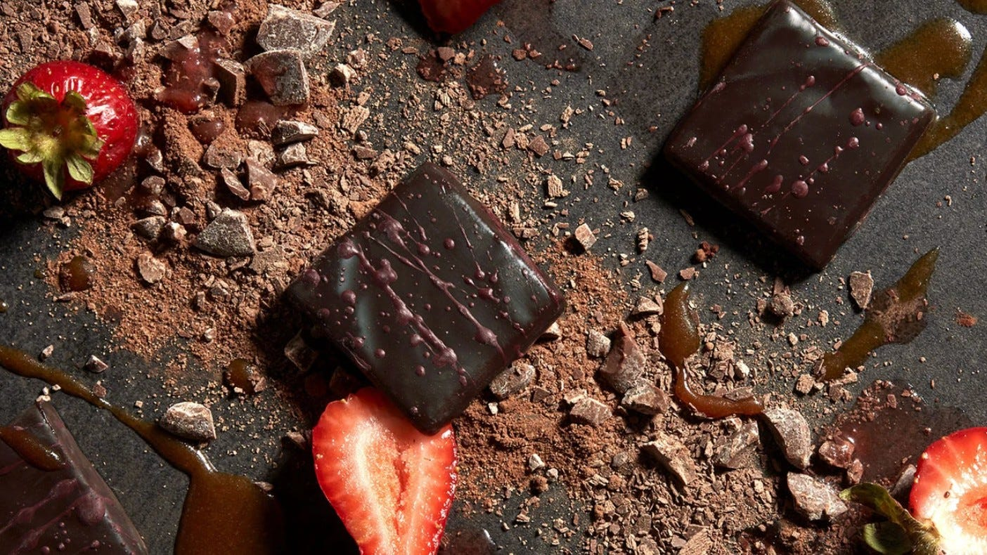 Two pieces of North South Confections fruit chocolate squares surrounded by sliced strawberries.