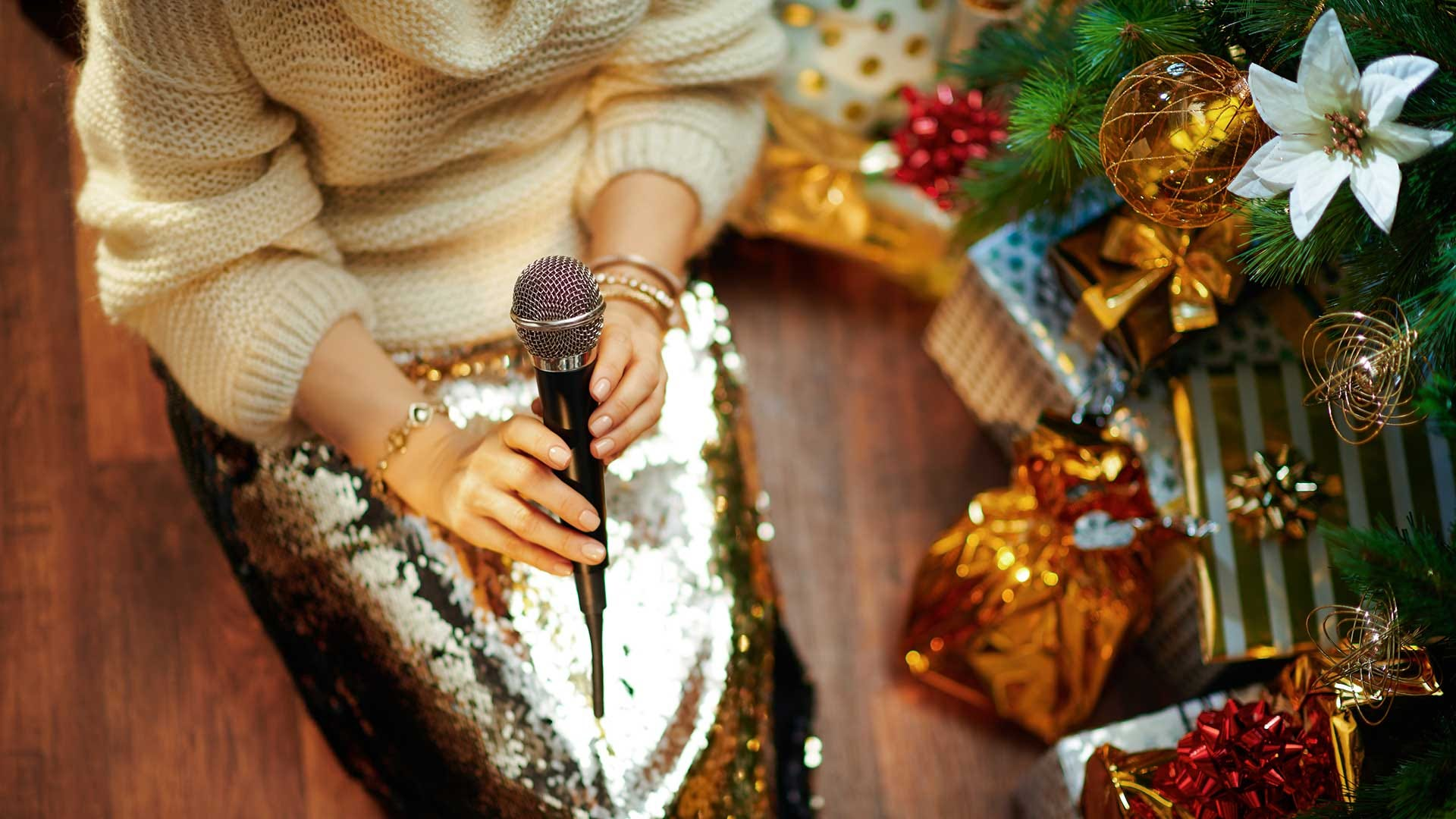 A woman sitting beside a Christmas tree, singing karaoke.