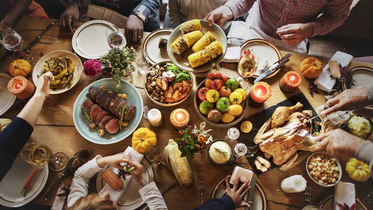 A wooden table filled with Thanksgiving foods, and people passing plates.