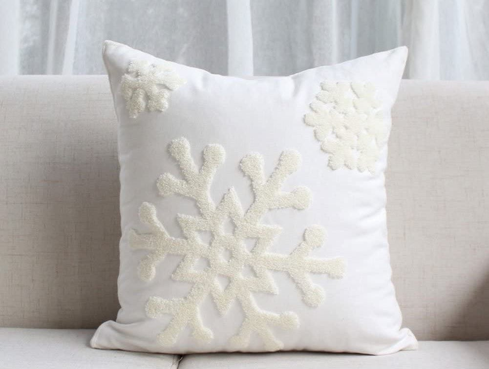 White snowflake pillow on a beige couch.