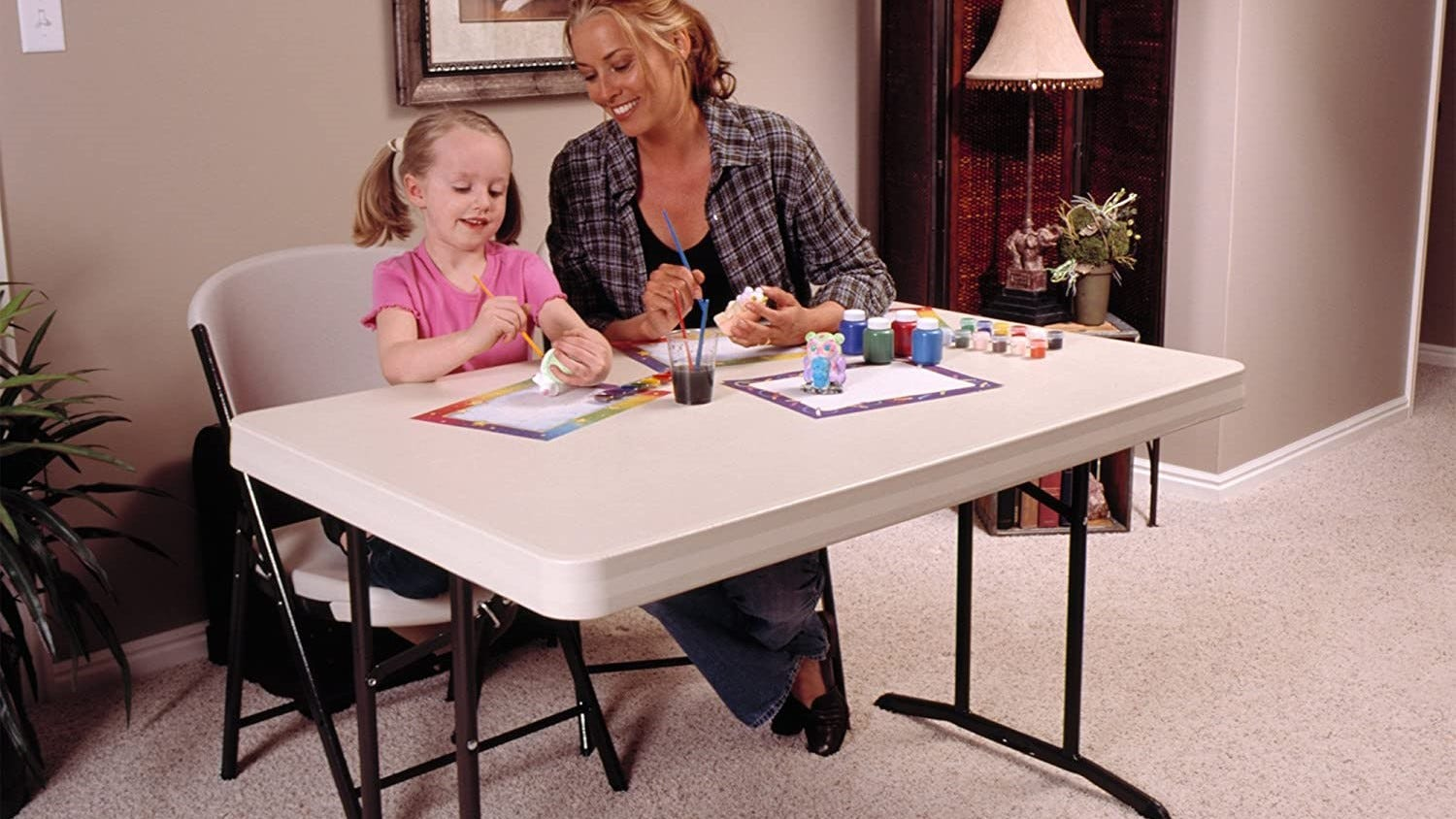 A woman and little girl sitting at a folding table working on crafts.
