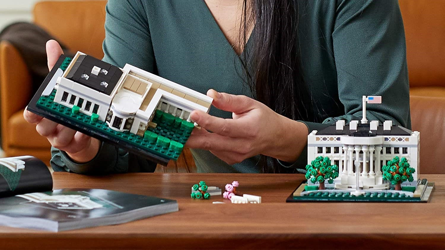 A woman assembling the LEGO White House on a table.