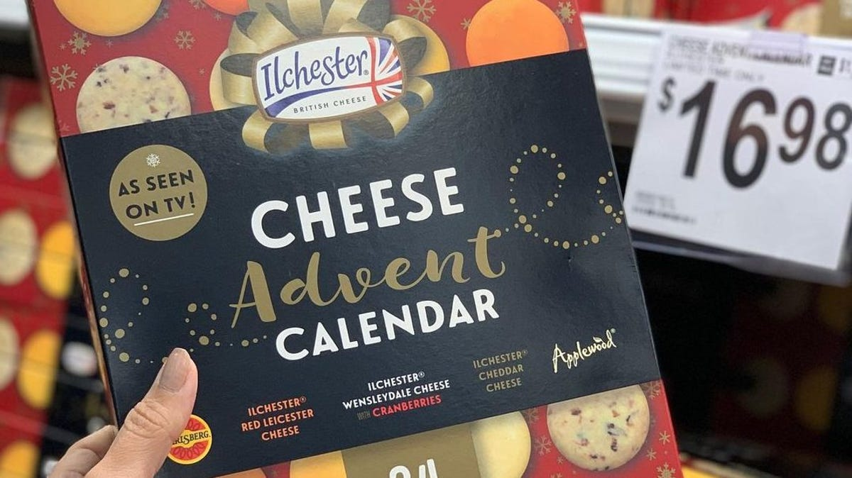 A woman holds up a boxed advent calendar of cheese.