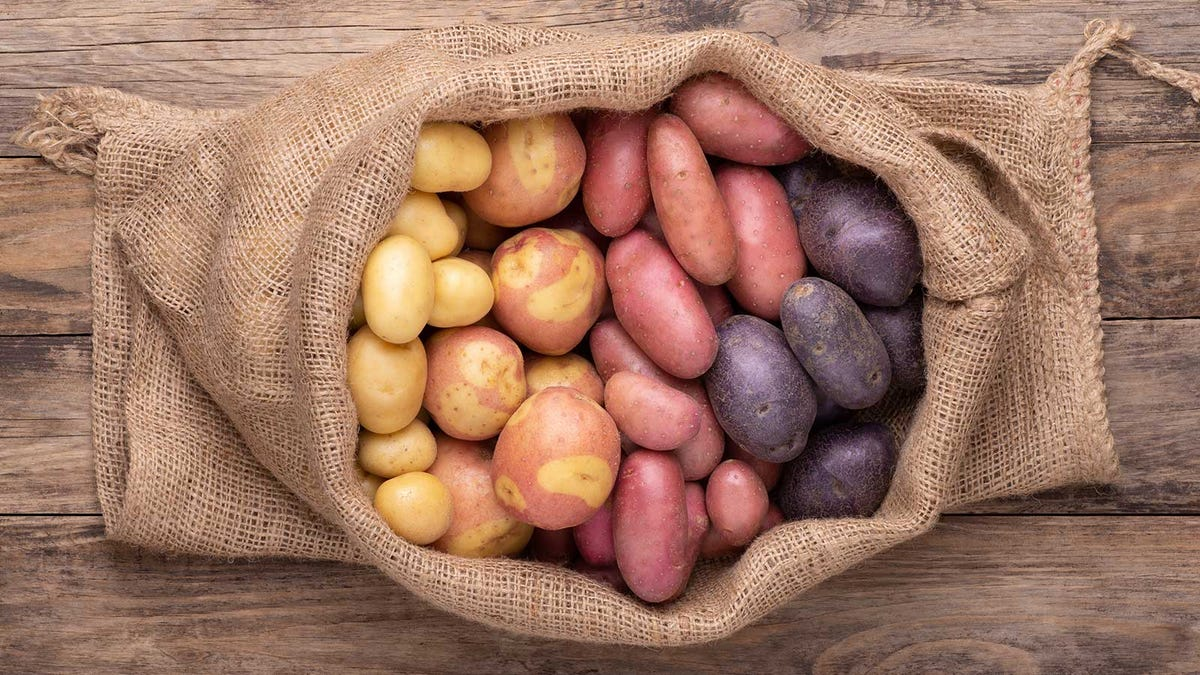 A rustic burlap bag on a wood table, filled with different varieties of potatoes.