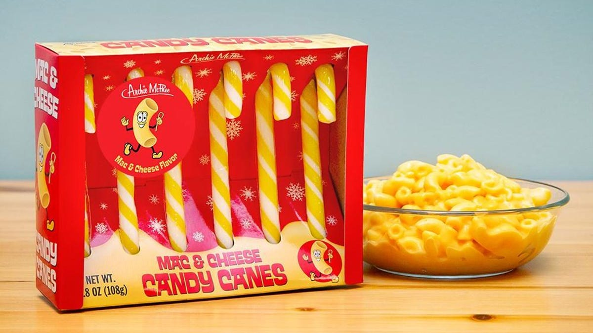 A box of macaroni and cheese flavored candy canes sits next to a bowl of macaroni and cheese.
