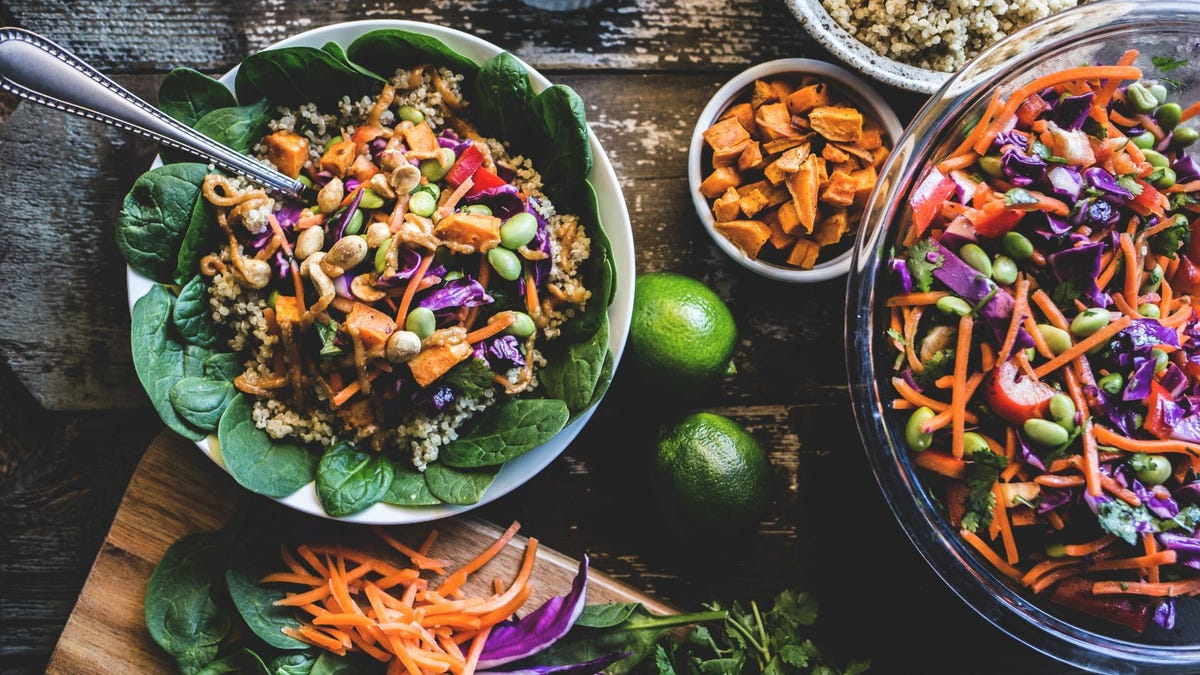 Two bowls filled with sliced vegetables over quinoa.