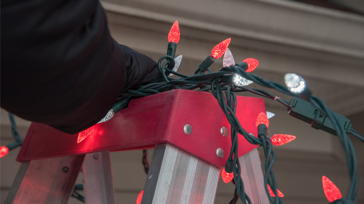 A person stands on a ladder to string up Christmas lights.
