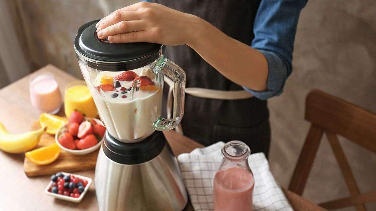 A woman using a blender to blend fruit and milk into a delicious smoothie.