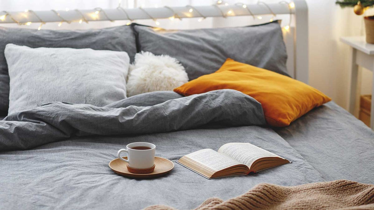 A cozy bed covered in warm blankets with lots of pillows, a book, and a cup off coffee.